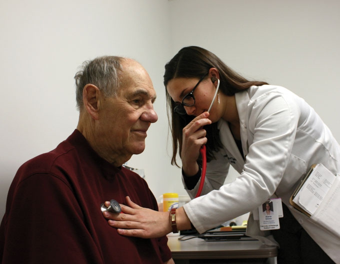 A Pitt medical student uses a stethoscope to listen to a patient's chest