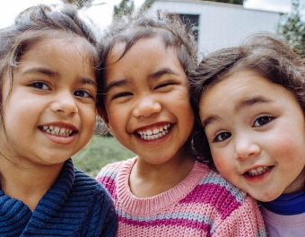 Three children smile at the camera